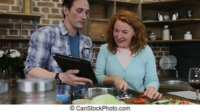 Woman Chopping Vegetables Looking At Tablet Computer Screen Talk With Man, Adult Couple Cooking In Kitchen Together