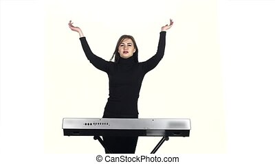 Woman claps her hands on electronic piano playing. Slow motion