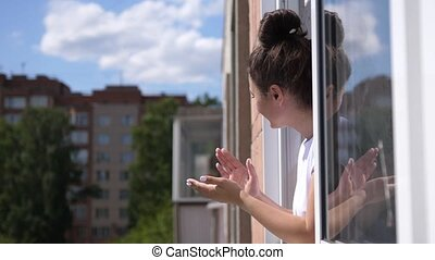 Woman claps his hands looking out the open window