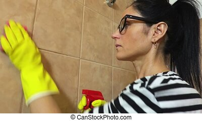 Woman clean bathroom tiles
