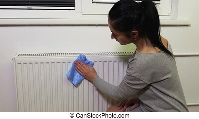 Woman clean dust from heating radiator