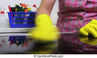 Woman clean electric cooker surface in kitchen