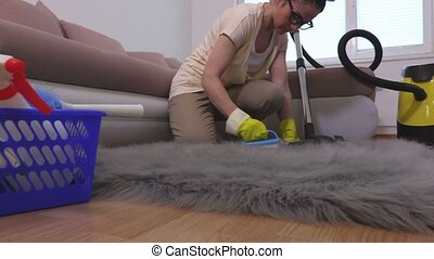 Woman clean faux fur rug with brush