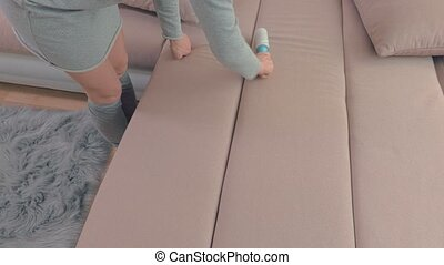 Woman clean sofa with lint roller