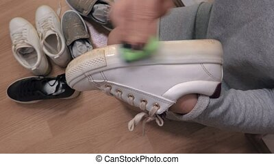 Woman clean sole of white sneakers