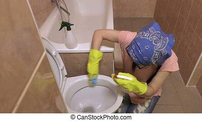 Woman clean toilet bowl