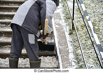 Woman cleaner shovels snow from street stairs