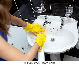 Woman cleaning a bathroom\'s sink with a sponge and...