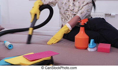 Woman cleaning a couch with a vacuum