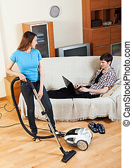 Woman cleaning at home while man with notebook