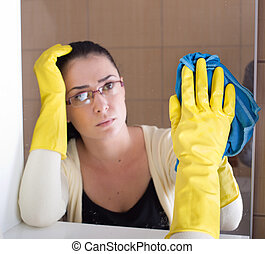 Woman cleaning bathroom mirror - Tired woman with rubber...