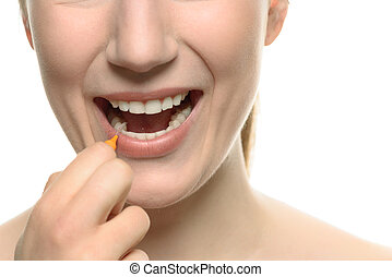 Woman cleaning between her teeth with an interdental brush