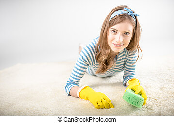 Woman cleaning carpet - Young woman in rubber gloves...