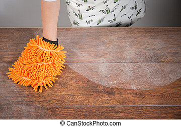 Woman cleaning dusty table with orange cleaner