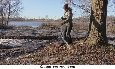 Woman cleaning edge of lake before season