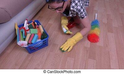 Woman cleaning floor near sofa
