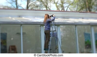 Woman cleaning glass house roof with high pressure tool in nature.