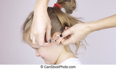 Woman cleaning her daughter's ear with a cotton swabs