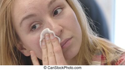 Woman cleaning her face with cotton pad.