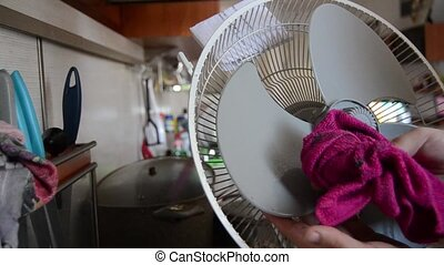 Woman cleaning home air cooling fan and showing dirthy...