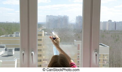 Woman cleaning home windows on high floor