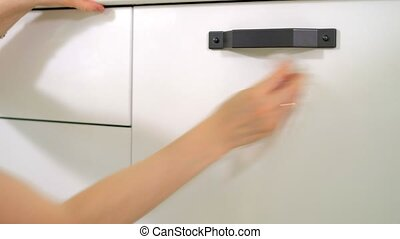 Woman cleaning kitchen cabinets with sponge and spray...