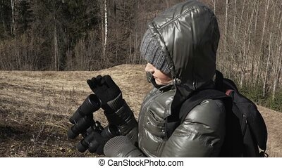 Woman cleaning lenses of binoculars at outdoors