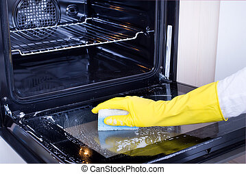 Woman cleaning oven - Close up of female hand with yellow...