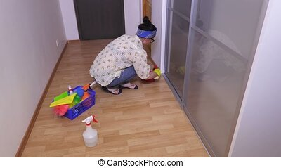 Woman cleaning rail of clothes closet