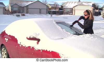 Woman cleaning snow off of car