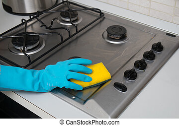 Woman cleaning stainless steel gas surface in  the kitchen at home