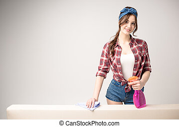 Woman cleaning surface - Young attractive woman holding...