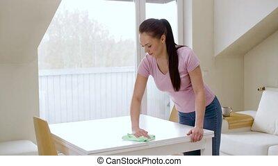 woman cleaning table with microfiber cloth at home -...