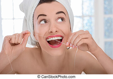 Woman cleaning teeth with floss