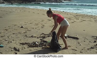 Woman cleaning the beach