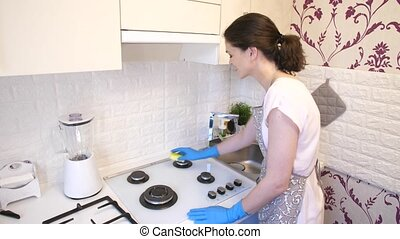 Woman cleaning the gas stove - Woman in protective gloves...