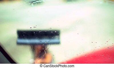 Woman cleaning truck window. Inside view.