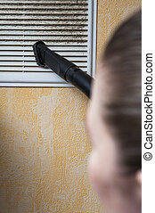 Woman cleaning ventilation grill with vacuum cleaner.