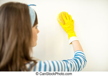 Woman cleaning wall - Rear view or young woman in rubber...