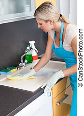 Woman Cleaning Worktop - Portrait Of Happy Woman Cleaning...