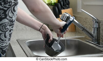 Woman cleans bowl in kitchen sink