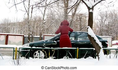 Woman cleans car from snow and pushes it that he went