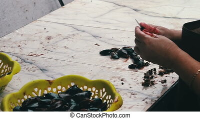Woman Cleans Mussels in the Fish Market - Woman cleans a...