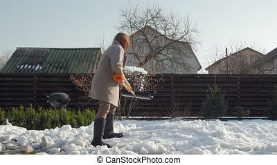 Woman cleans snow with shovel in the yard
