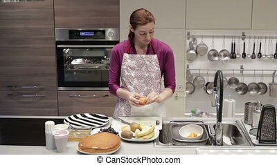 Woman cleans tangerine in the kitchen - The woman in an...