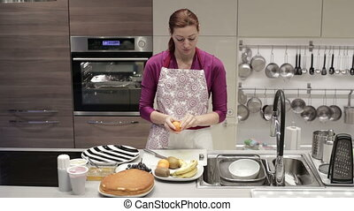 Woman cleans tangerine peel - The woman in an apron in the...