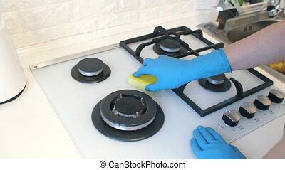 Woman cleans the gas stove - Woman in protective gloves...