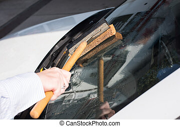 Woman cleans the windshield of her car