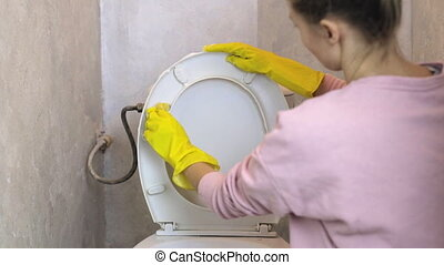 Woman cleans white toilet bowl with a sponge in yellow rubber gloves