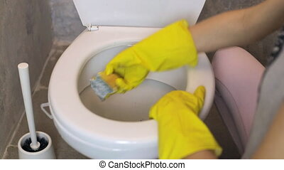 Woman cleans white toilet with a sponge